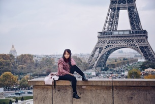 Portrait Of Young Woman Sitting Against Eiffel Towerの写真素材 [FYI04448448]