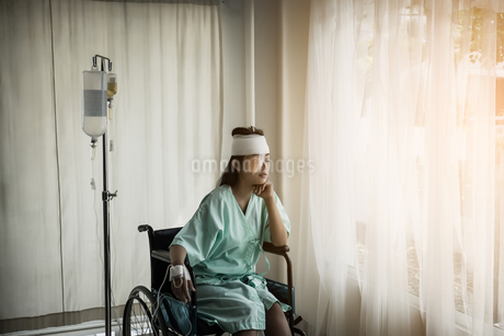 Woman With Physical Injury Sitting On Wheelchair By Iv Drip At Hospitalの写真素材 [FYI04449379]