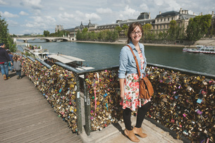Portrait Of Woman Standing By Love Locks On Railing By Riverの写真素材 [FYI04449498]