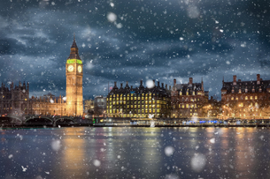Illuminated City By River Against Sky At Night During Snowfallの写真素材 [FYI04450886]