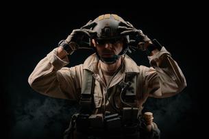 Man Wearing Helmet Against Black Backgroundの写真素材 [FYI04451554]