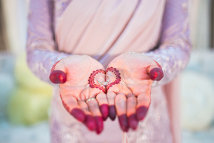 Midsection Of Bride With Henna Tattoo On Her Hands Holding Wedding Ringの写真素材 [FYI04451867]
