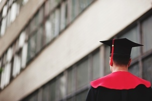 Rear View Of Man Wearing Graduation Gown Against Buildingの写真素材 [FYI04451928]