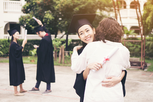 Cheerful Woman In Graduation Gown Embracing Mother While Standing Outdoorsの写真素材 [FYI04452125]
