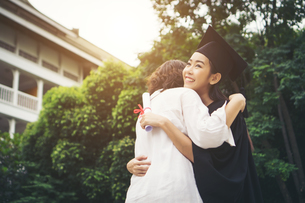 Cheerful Woman In Graduation Gown Embracing Mother While Standing Outdoorsの写真素材 [FYI04452127]