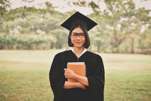 Young Woman In Graduation Gown Holding Booksの写真素材 [FYI04453257]
