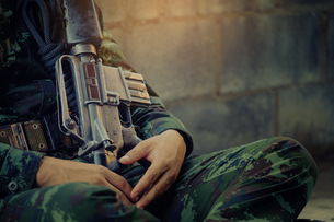 Midsection Of Army Soldier Sitting With Weaponの写真素材 [FYI04459804]