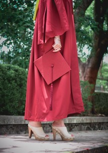 Low Section Of Woman Wearing Graduation Gown Holding Mortarboardの写真素材 [FYI04461471]