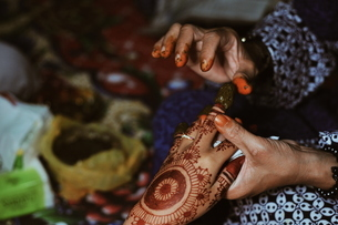 Cropped Hands Of Artist Applying Henna Tattoo On Woman Hand During Wedding Ceremonyの写真素材 [FYI04463558]