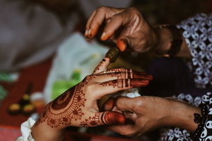 Cropped Hands Of Artist Applying Henna Tattoo On Woman Hand During Wedding Ceremonyの写真素材 [FYI04463561]