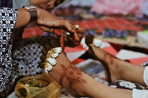Woman Applying Henna Tattoo On Bride Leg During Wedding Ceremonyの写真素材 [FYI04463562]