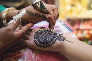 Close-up Of Artist Applying Henna Tattoo On Handの写真素材 [FYI04463661]