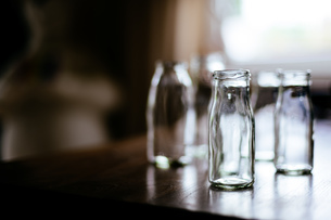 Close-up Of Empty Glass Bottles On Tableの写真素材 [FYI04466353]