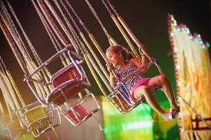 Smiling Girl Looking Away While Sitting On Chain Swing Rideの写真素材 [FYI04466423]