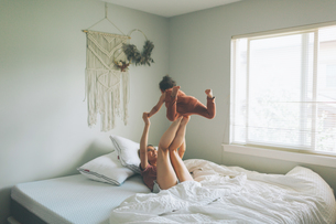Cheerful Mother And Daughter Spending Leisure Time On Bed At Homeの写真素材 [FYI04466808]