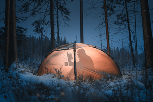 Shadow Of Man Reading Book In Illuminated Tent At Snow Covered Forest During Nightの写真素材 [FYI04466824]