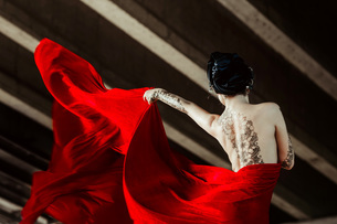 Rear View Of Tattooed Seductive Fashion Model Holding Red Fabricの写真素材 [FYI04467884]