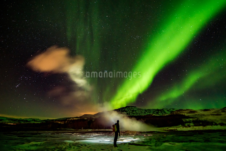 Man Standing By Geyser Against Geomagnetic Storm In Sky At Nightの写真素材 [FYI04468281]