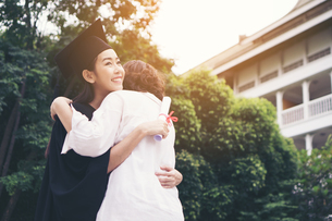 Cheerful Woman In Graduation Gown Embracing Mother While Standing Outdoorsの写真素材 [FYI04469376]