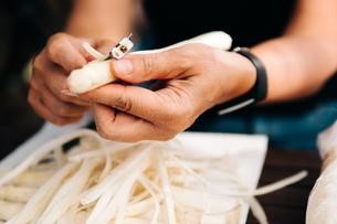 Midsection Of Woman Peeling Vegetableの写真素材 [FYI04469406]