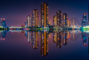 Reflection Of Illuminated Buildings In City At Nightの写真素材 [FYI04470761]