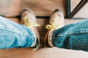 Low Section Of Man Wearing Shoes On Hardwood Floorの写真素材 [FYI04471490]