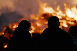 Rear View Of Silhouette People By Fire At Nightの写真素材 [FYI04472523]