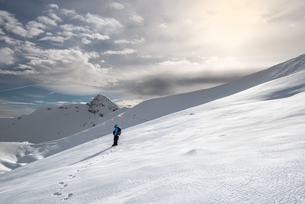 Side View Of Man Skiing On Snowcapped Mountains Against Skyの写真素材 [FYI04472680]
