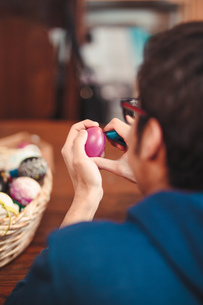 Close-up Of Man Decorating Easter Egg At Homeの写真素材 [FYI04472787]