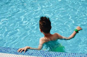 Rear View Of Shirtless Boy Swimming In Poolの写真素材 [FYI04472854]