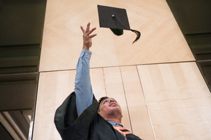 Low Angle View Of Man Throwing Mortarboard While Standing Against Wallの写真素材 [FYI04473621]
