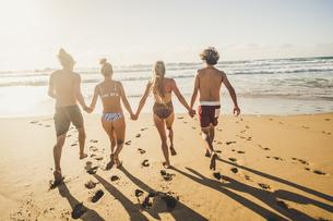 Full Length Rear View Of Friends Running On Beachの写真素材 [FYI04473659]