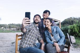 Happy Friends Taking Selfie In Rural Area Against Clear Skyの写真素材 [FYI04473686]