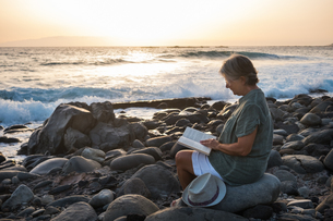 Woman Reading Book While Sitting On Rocks At Beach During Sunsetの写真素材 [FYI04474776]