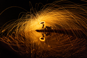 Silhouette Man Spinning Wire Wool At Nightの写真素材 [FYI04475074]
