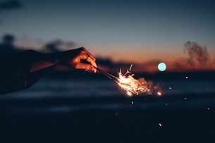 Cropped Hand Holding Burning Sparkler At Sunset Against Skyの写真素材 [FYI04476347]