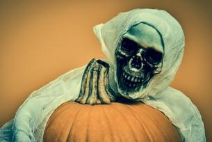 Close-up Of Halloween Skull With Pumpkin Against Orange Backgroundの写真素材 [FYI04476794]