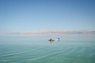 Man Floating In Dead Sea Against Clear Blue Skyの写真素材 [FYI04476940]