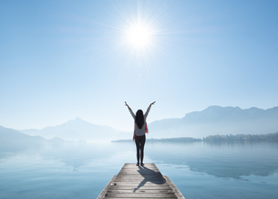 Full Length Rear View Of Woman With Arms Raised Standing On Pier By Lake Against Sky During Sunny Daの写真素材 [FYI04476975]