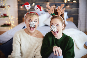 Cheerful Sisters Wearing Headbands At Home During Christmasの写真素材 [FYI04477120]