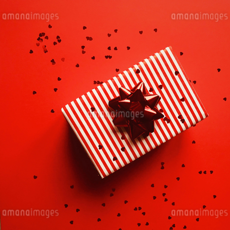 Directly Above Shot Of Gift Box And Heart Shape Confetti On Red Backgroundの写真素材 [FYI04477324]