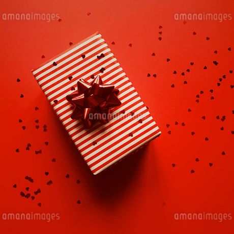 Directly Above Shot Of Gift Box And Heart Shape Confetti On Red Backgroundの写真素材 [FYI04477326]