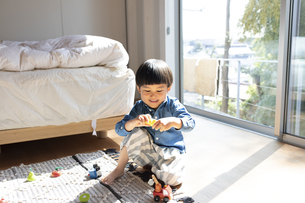 日当たりの良い部屋で遊ぶ男の子の写真素材 [FYI04477528]