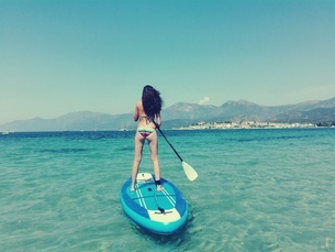 Rear View Of Woman Paddleboarding In Sea Against Blue Skyの写真素材 [FYI04477726]