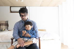 寝室でスマホを見る親子の写真素材 [FYI04477867]