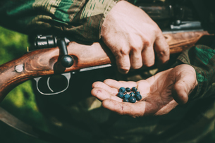 Midsection Of Army Solider Holding Berries While Standing Outdoorsの写真素材 [FYI04477893]