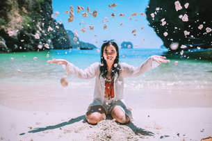 Smiling Young Woman Throwing Sand At Beach During Sunny Dayの写真素材 [FYI04477899]