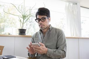 スマホを操作する男性の写真素材 [FYI04477969]