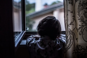 Rear View Of Woman Looking Through Window At Homeの写真素材 [FYI04478291]