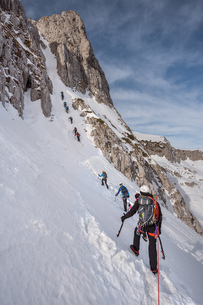Rear View Of Hikers On Snow Capped Mountainの写真素材 [FYI04478569]